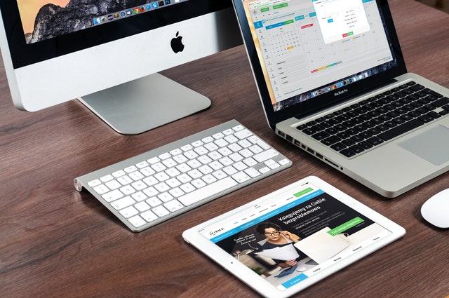 na stole stojící stolní PC a ležící notebook a tablet