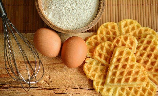 vafle ve tvaru srdíčka, dvě vajíčka, na stole ingredience, mouka, metlička